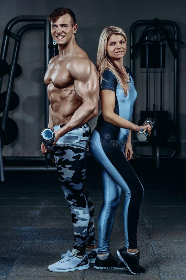 Sprawności fizycznej para - kobieta i mężczyzna z dumbbells w gym obrazy royalty free