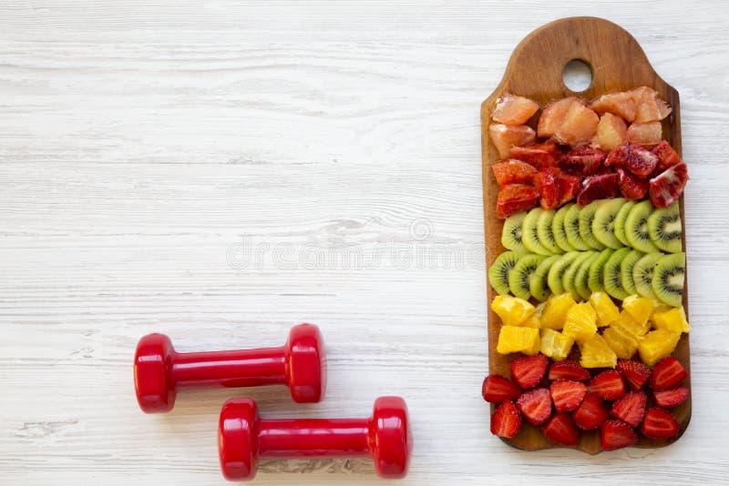 Sprawności fizycznej pojęcie, dieta plan Siekać owoc na pokładzie, dumbbells na białym drewnianym tle, odgórny widok obrazy stock