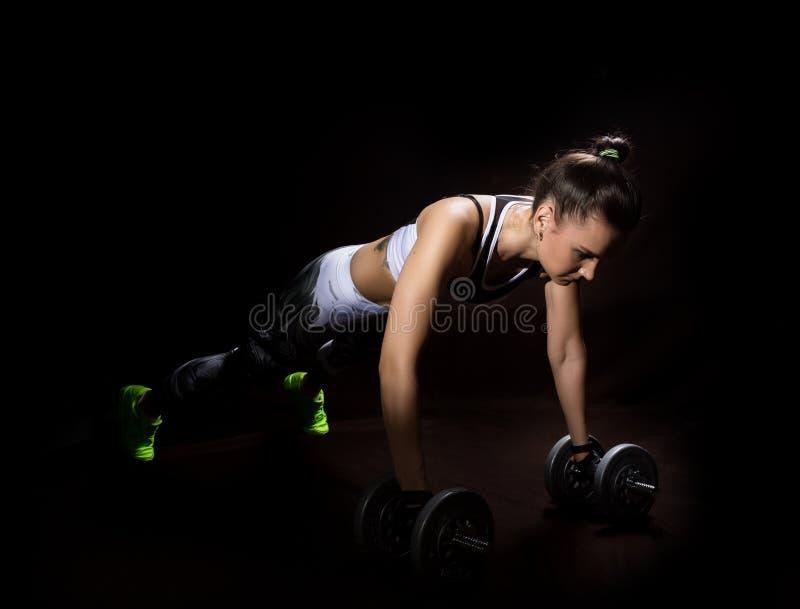Sprawności fizycznej seksowna dziewczyna na ciemnym tle Atleta robi ćwiczeniom w gym obrazy royalty free