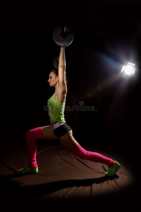 Sprawności fizycznej seksowna dziewczyna z barbell na ciemnym tle Atleta robi ćwiczeniom w gym zdjęcie stock