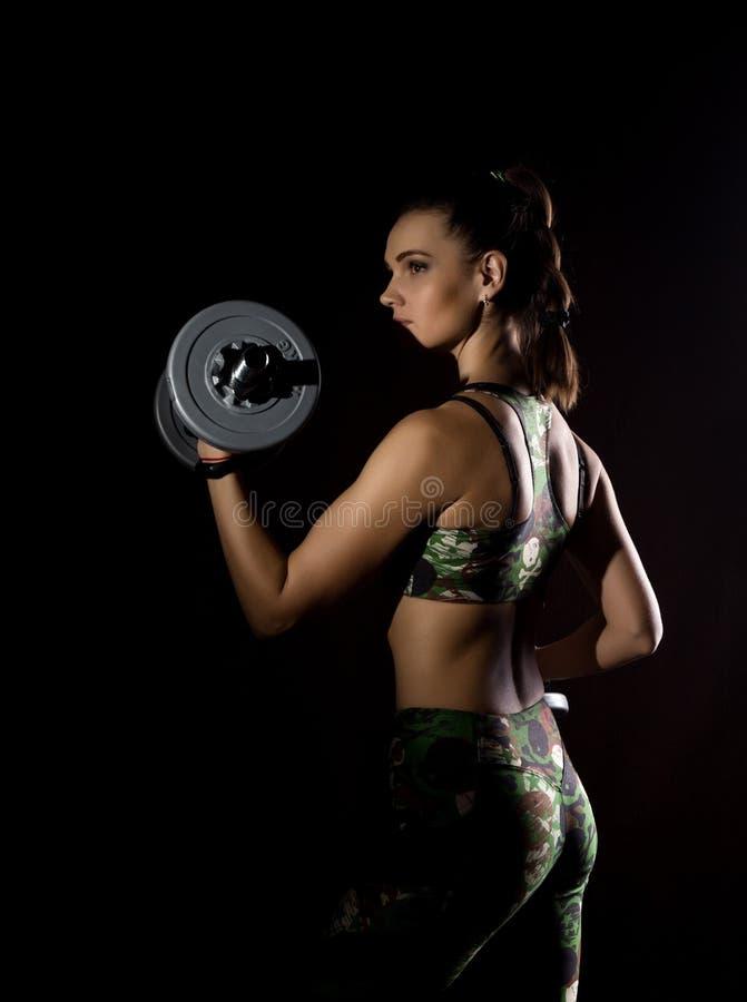 Sprawności fizycznej seksowna dziewczyna z dumbbells na ciemnym tle Atleta robi ćwiczeniom w gym zdjęcia royalty free