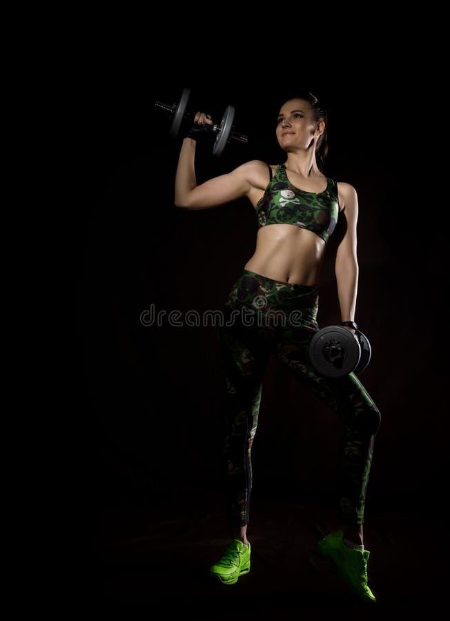 Sprawności fizycznej seksowna dziewczyna z dumbbells na ciemnym tle Atleta robi ćwiczeniom w gym zdjęcie stock