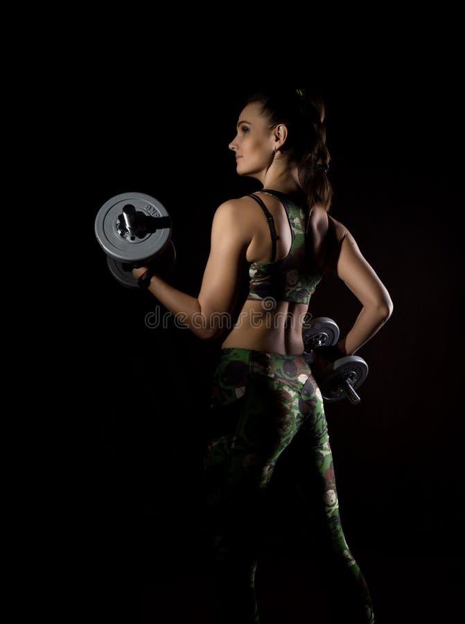 Sprawności fizycznej seksowna dziewczyna z dumbbells na ciemnym tle Atleta robi ćwiczeniom w gym obraz stock