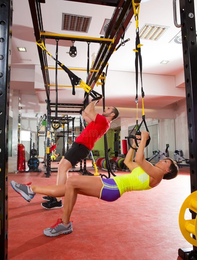Sprawności fizycznej TRX ćwiczenia szkoleniowe przy gym mężczyzna i kobietą zdjęcia royalty free