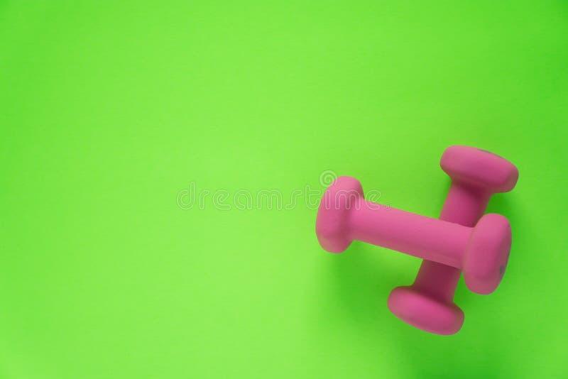 Sprawności fizycznej wyposażenie z kobiet menchiami weights/dumbbells odizolowywających na wapno zieleni tle z copyspace zdjęcia stock