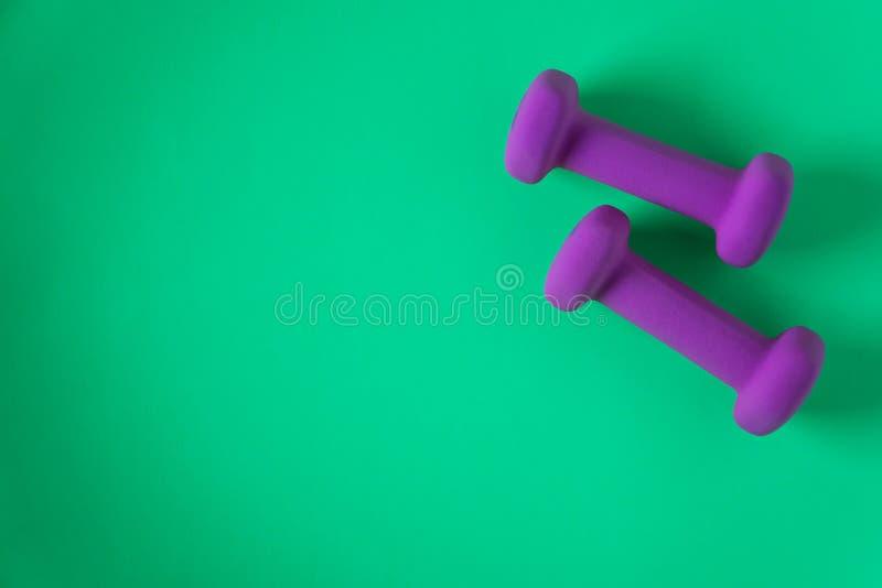Sprawności fizycznej wyposażenie z kobiet purpur weights/dumbbells odizolowywającymi na cyraneczki zieleni tle z copyspace zdjęcia royalty free