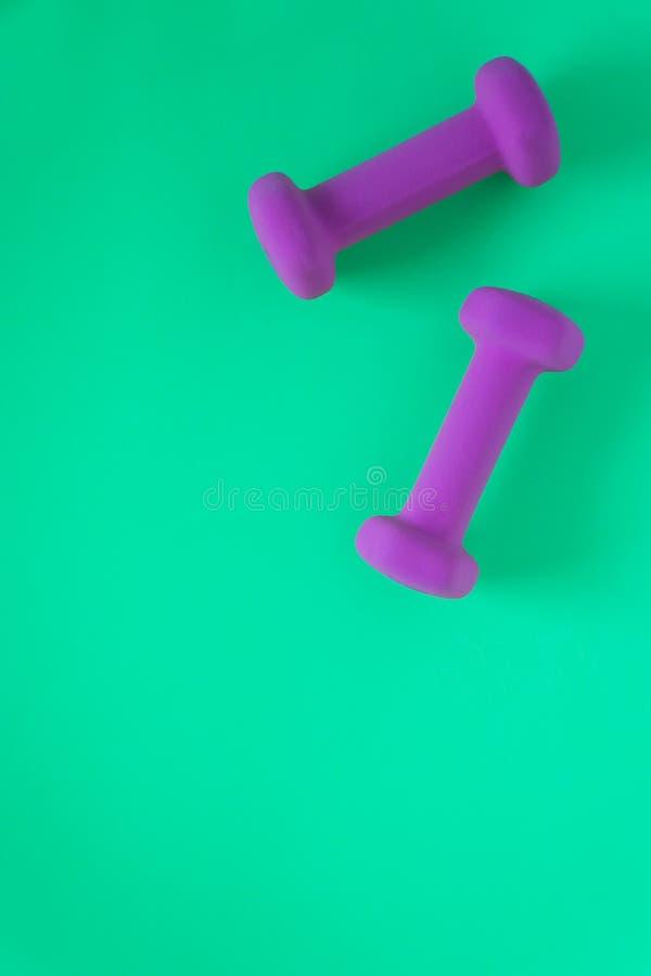 Sprawności fizycznej wyposażenie z kobiet purpur weights/dumbbells odizolowywającymi na cyraneczki zieleni tle z copyspace obraz royalty free