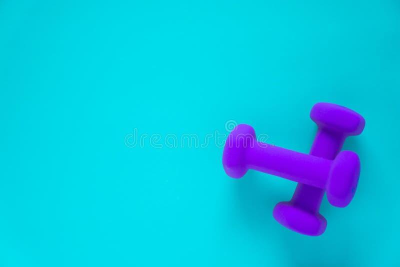 Sprawności fizycznej wyposażenie z kobiet purpurami weights/dumbbells odizolowywających na lekkim nieba błękita tle z copyspace zdjęcie stock