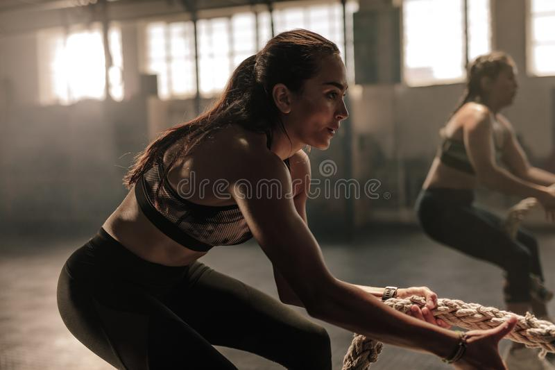 Sprawności fizycznych kobiety ciągnie arkanę przy gym klasą fotografia royalty free