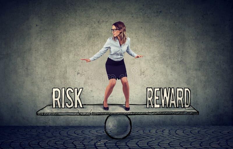 Sprawny młody biznesowej kobiety równoważenie między nagrodą i ryzykiem obrazy royalty free