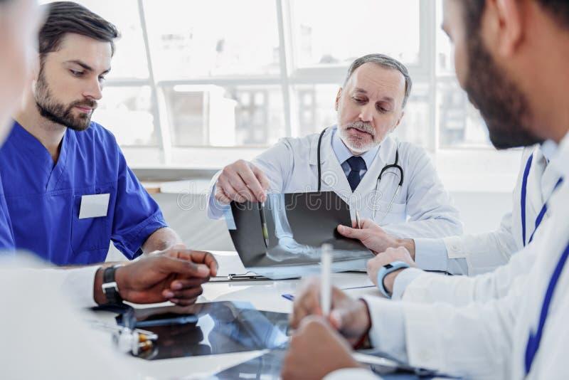 Sprawny zaopatrzenie medyczne dyskutuje promieniowanie rentgenowskie fotografię zdjęcia stock