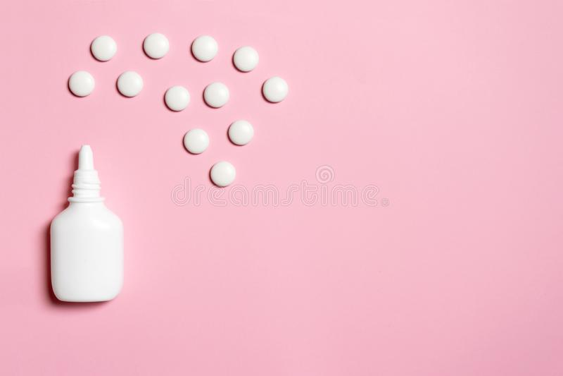 Spray nasale di plastica bianco con le compresse su fondo rosa - sinusite, geniantritis, rinite ed altre malattie degli organi OT immagini stock