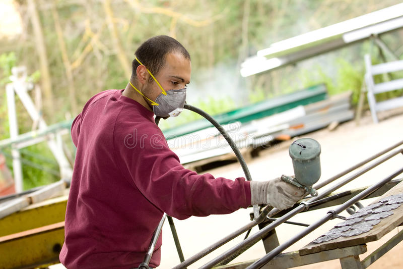 Spray painter. Painting a gate royalty free stock images