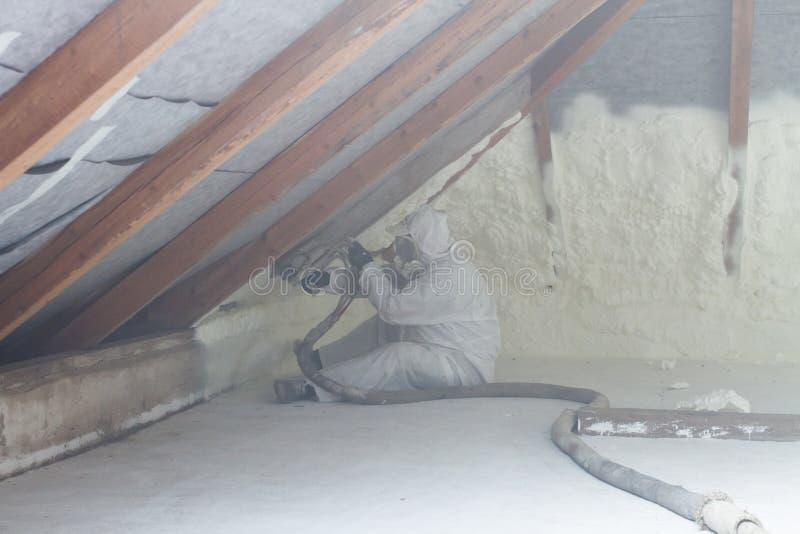 Spray polyurethane foam for roof. Technician spraying foam insulation using plural component gun for polyurethane foam, inside stock photos