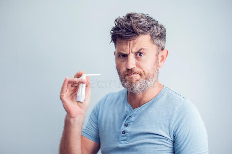 Spray for sore throat. Photo of a man who treats his throat with stock photo