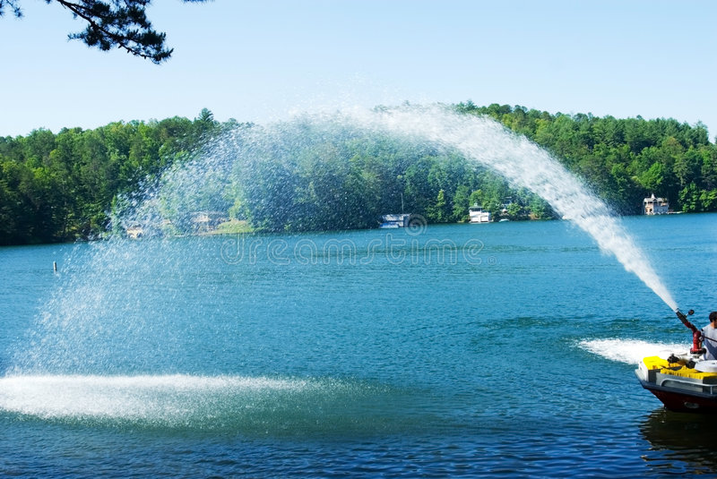 Spray of Water From Fire Boat. A fire boat on the lake testing the equipment stock image