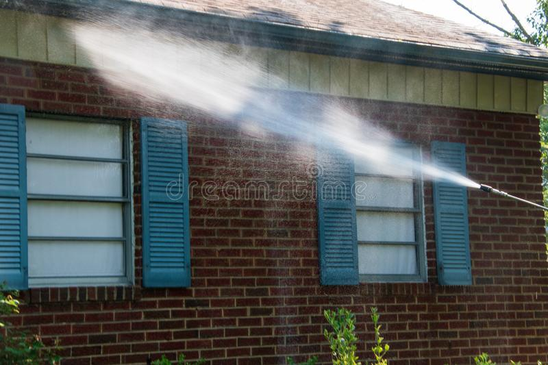 Spray of water on siding and brick work on the side of a building. There are two windows with blue shutters. stock photography