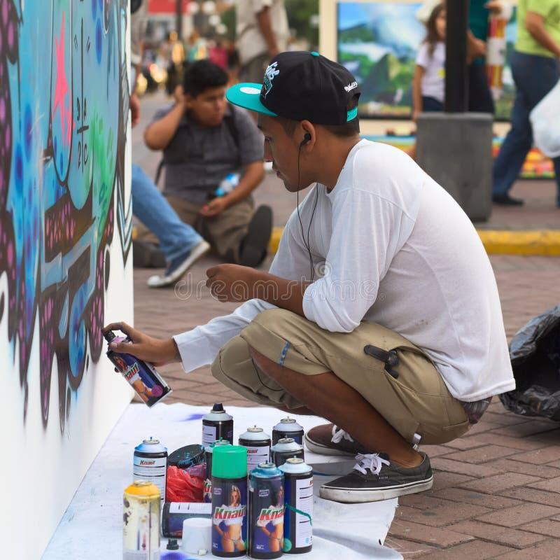 Sprayer on the Latir Latino Festival in Lima, Peru. LIMA, PERU - MARCH 3, 2012: Unidentified young man spraying a wall on the Latir Latino, the first Latin royalty free stock photos