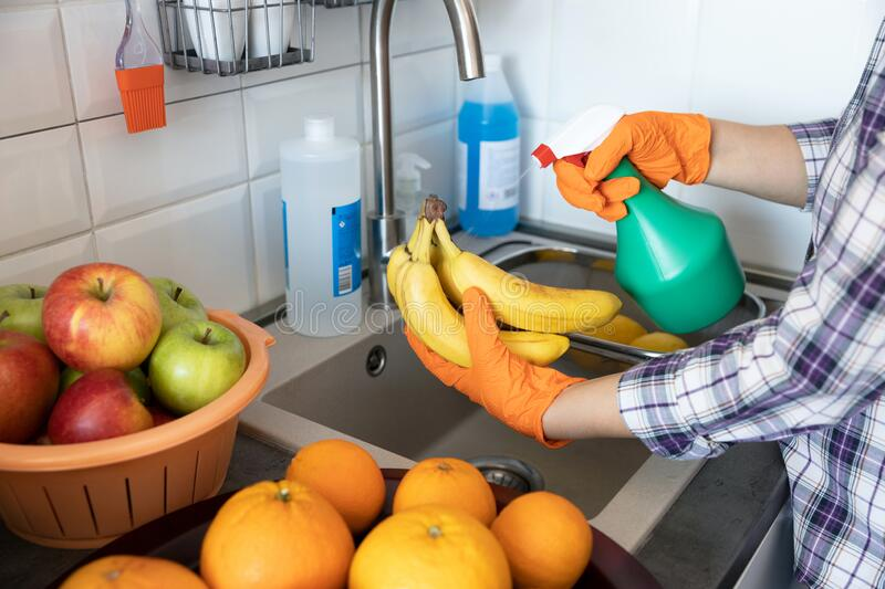 Spraying disinfecting chemical on the fruit in the kitchen. COVID-19 Coronavirus pandemic concept. stock image