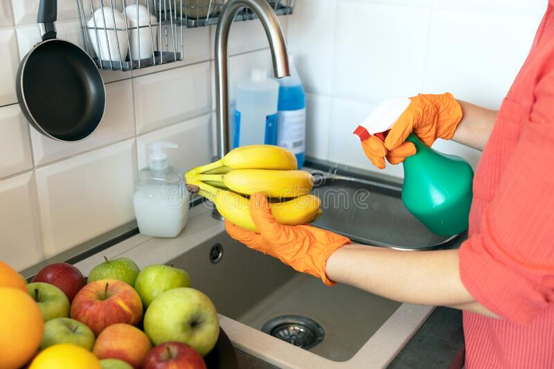 Spraying disinfecting chemical on the fruit in the kitchen. COVID-19 Coronavirus pandemic concept. stock photos