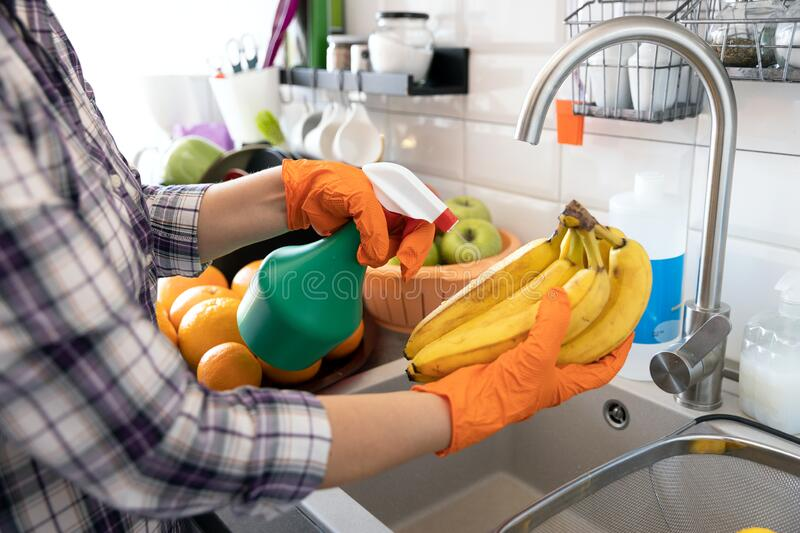 Spraying antibacterial chemical on the fruit in the kitchen. COVID-19 Coronavirus pandemic concept. royalty free stock photo