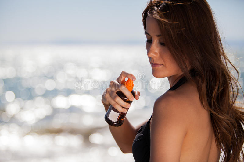 Spraying some tanning lotion. Young woman spraying some tanning lotion on her shoulder on a sunny day stock image