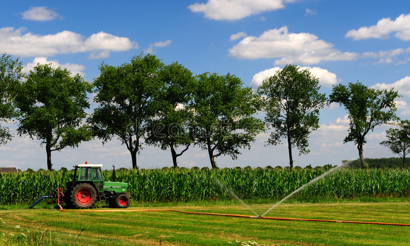 Spraying tractor. Tractor on the field spraying water royalty free stock photo