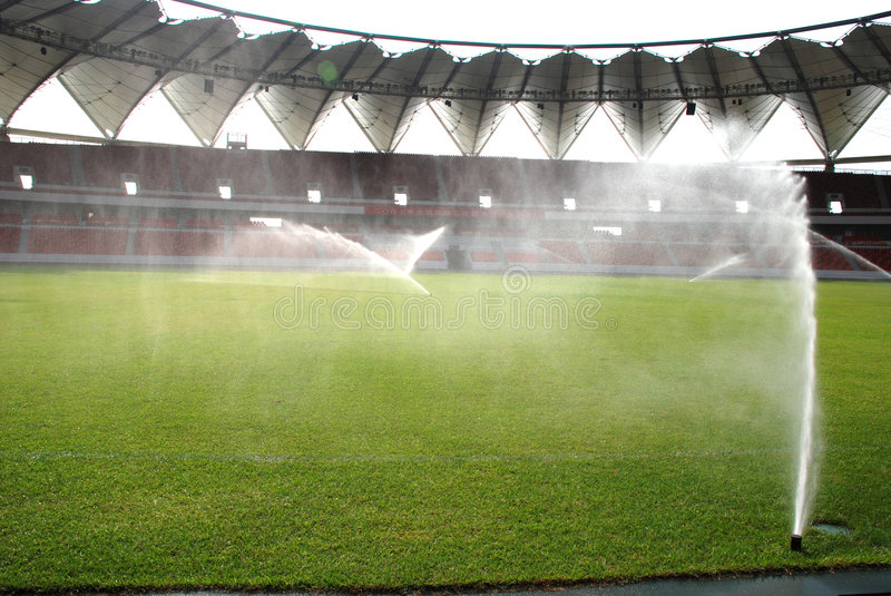 Spraying water. Meadow maintenance,Auto-irregating and spraying water on a football pitch stock photography