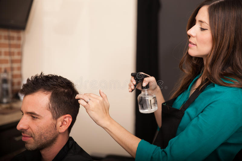 Spraying water for a haircut. Cute young hairstylist spraying some water on a client's hair in a hair salon royalty free stock photography
