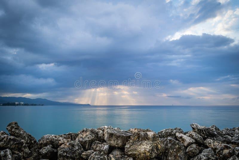 Sprazzo di sole attraverso le nuvole della pioggia persistente al tramonto Montego Bay, Giamaica fotografie stock libere da diritti