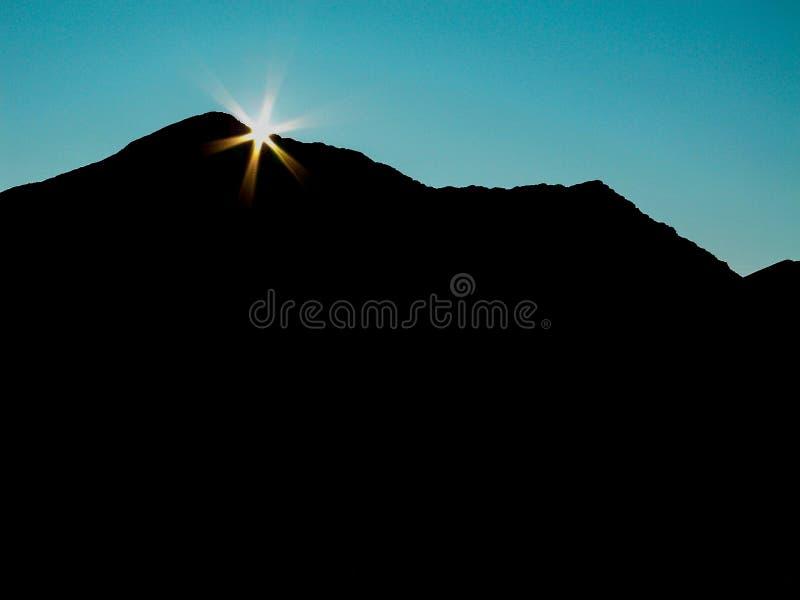 Sprazzo di sole sopra la spalla della cima della montagna fotografia stock libera da diritti