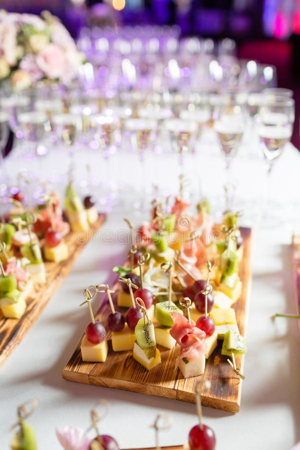 Furshet. Table top full of glasses of sparkling white wine with canapes and antipasti in the background. champagne. Spread of alcoholic beverages for celebration stock images