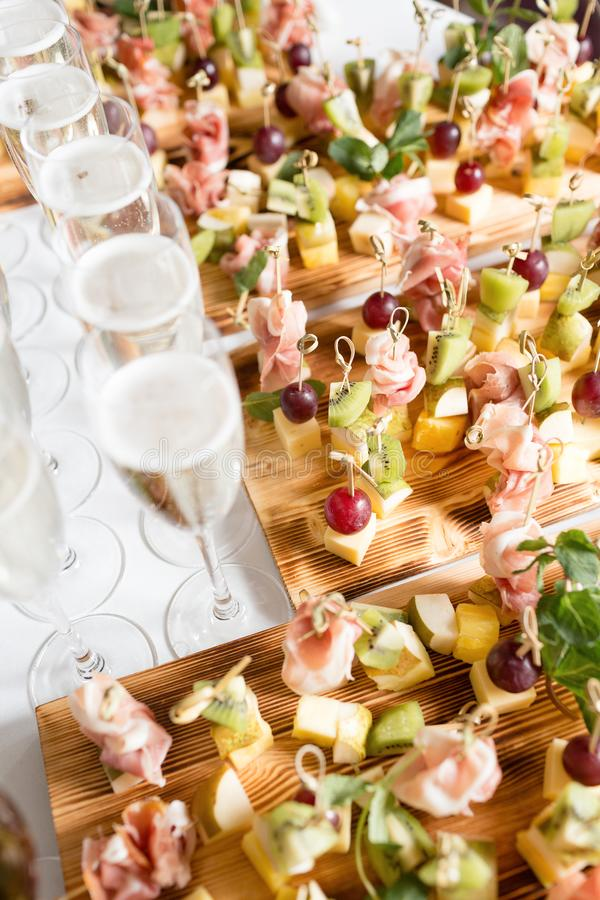 Furshet. Table top full of glasses of sparkling white wine with canapes and antipasti in the background. champagne. Spread of alcoholic beverages for celebration stock photo
