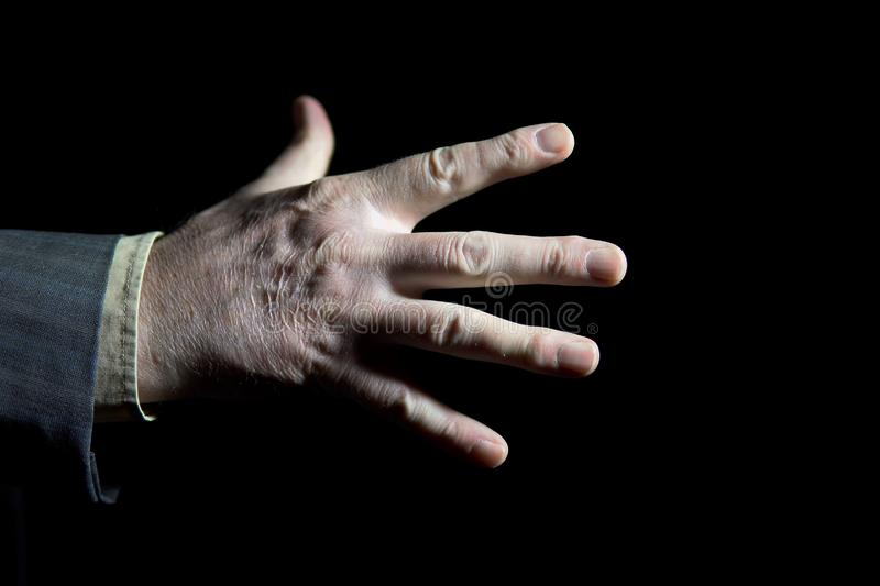 Spread fingers of an elderly man on black background stock images