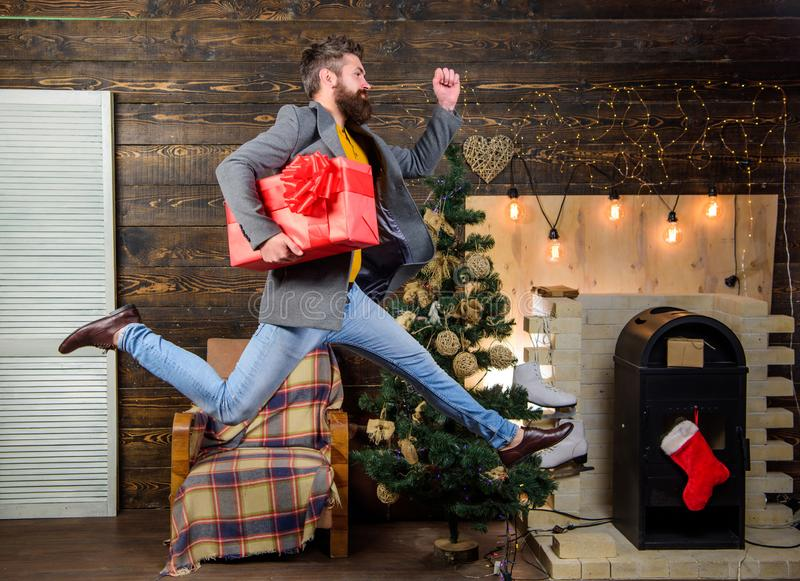 Spread happiness and joy. Bearded guy in motion jump. Delivery christmas present. Gifts delivery. Still have time. Delivery service. Christmas is coming. Man royalty free stock image
