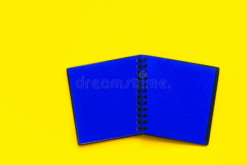 Spread of open blank black notepad with blue pages on bright yellow background. Trendy funky style vibrant colors. Business. Education marketing concept. Mockup royalty free stock photography