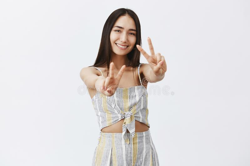 Spread peace and love across globe. Portrait of charming happy girlfriend in matching top and shorts, pulling hands royalty free stock photography