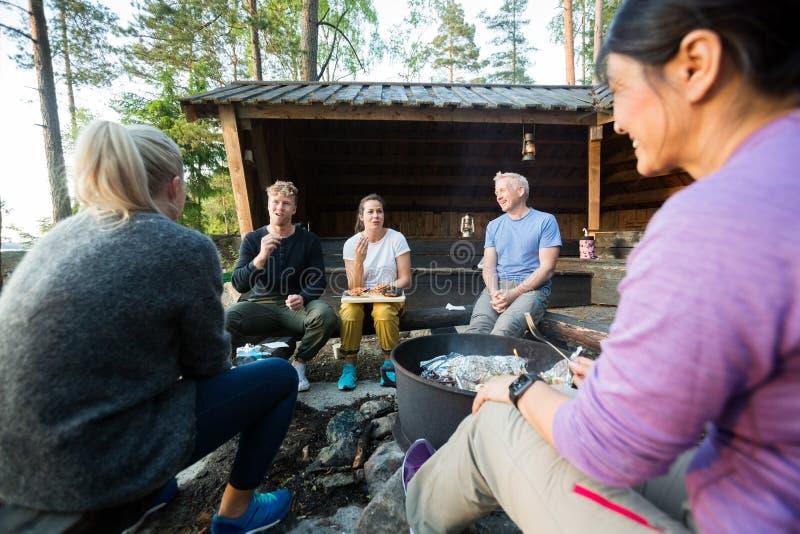 Sprechende Freunde beim Essen des Lebensmittels durch Firepit im Wald lizenzfreies stockfoto