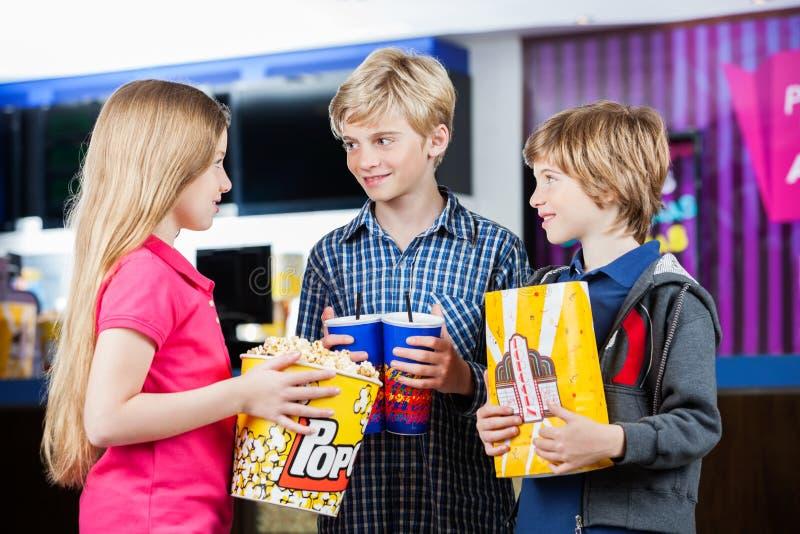 Sprechende Geschwister beim Halten von Snäcken am Kino stockfoto