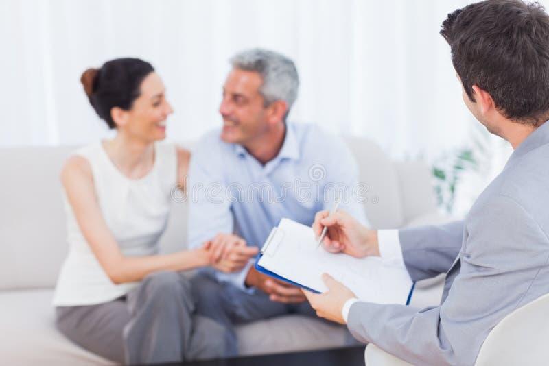 Sprechende Paare, während Verkäufer Vertrag hält lizenzfreie stockfotos
