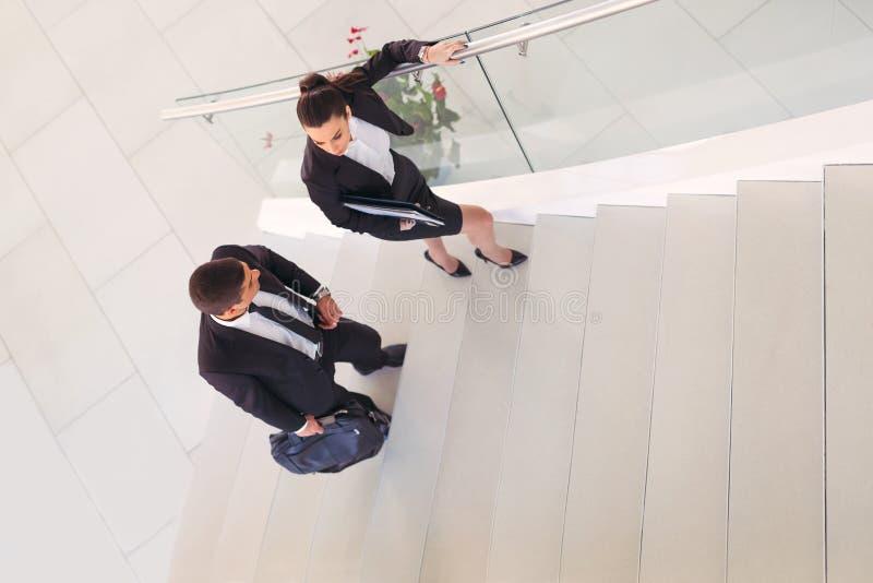 Sprechende Wirtschaftler, wie sie in das Büro gehen lizenzfreie stockfotografie