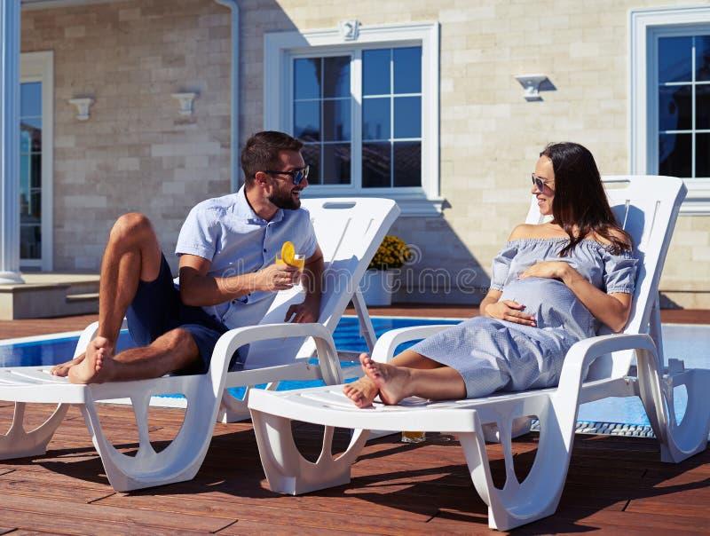 Sprechendes verheiratetes Paar beim Stillstehen nahe Pool lizenzfreies stockfoto
