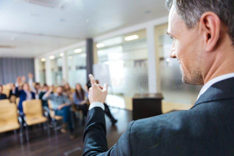 Sprecher, der auf Publikum auf Geschäftskonferenz zeigt lizenzfreie stockbilder