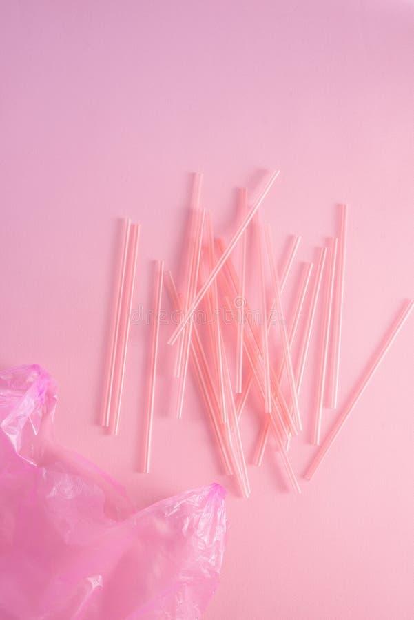 Spreco di plastica variopinto in una borsa di immondizia rosa come ciarpame monouso riciclabile di inquinamento della coltelleria immagine stock libera da diritti
