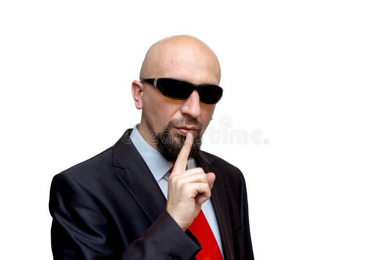 Spreek niet, de stille, taaie kale mens met donkere glazen houden stock fotografie