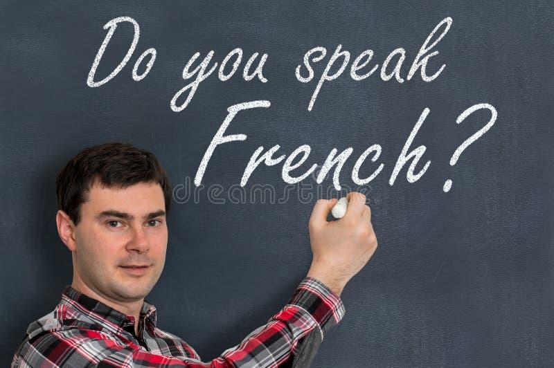 Spreekt u het Frans? Mens die met krijt op bord schrijven stock foto
