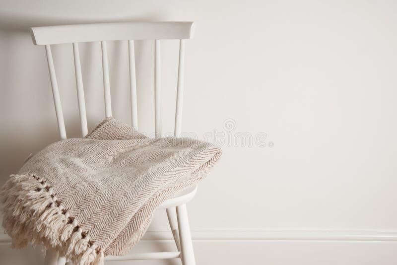 Sprei of deken op witte uitstekende stoel, minimalistic stijl huishouden De ruimte van het exemplaar royalty-vrije stock afbeeldingen