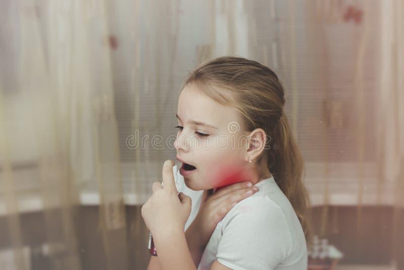 Sprej för öm hals Foto av en flicka som behandlar hennes hals med en sprej Begreppet av hälsa och sjukdomen royaltyfri fotografi