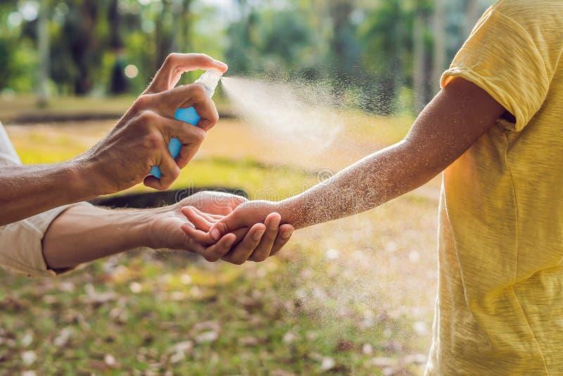 Sprej för farsa- och sonbruksmygga Bespruta krypimpregneringsmedlet på utomhus- hud arkivfoton