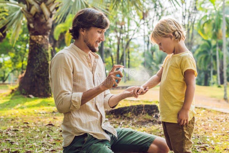 Sprej för farsa- och sonbruksmygga Bespruta krypimpregneringsmedlet på utomhus- hud arkivfoto